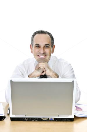 Businessman at his desk on white background stock photo, Happy businessman sitting at his desk isolated on white background by Elena Elisseeva