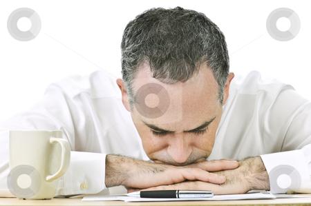 Businessman resting head on hands stock photo, Businessman taking a break at his desk by Elena Elisseeva
