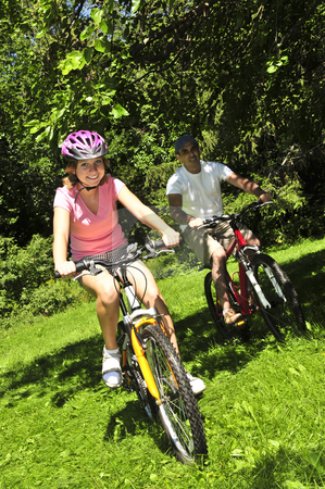 Family riding bicycles stock photo, Teenage girl and her father riding bicycles in summer park by Elena Elisseeva