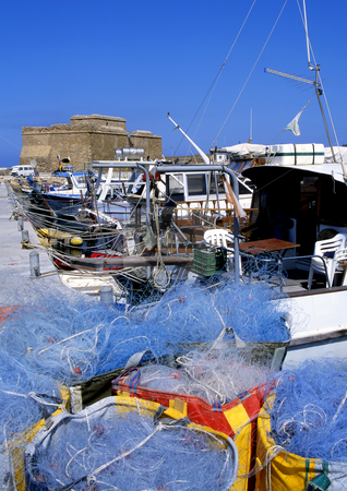 Paphos fort stock photo, Fishing nets and boats with Paphos fort, Cyprus in the background by Paul Phillips