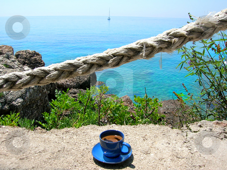 Morning coffee on terrace stock photo, Cup of coffee on stone terrace in sea cafe with rope fence by Julija Sapic