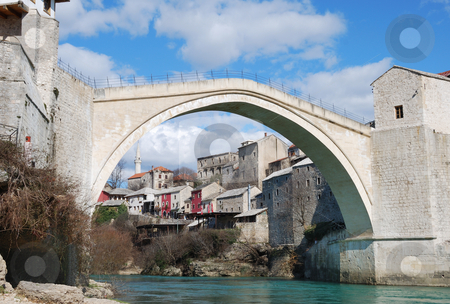Mostar Old Bridge stock photo, Old Bridge in Mostar, Bosnia and Herzegovina with the old town and blue sky in background by Denis Radovanovic