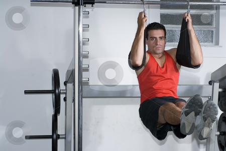 Hanging Crunches stock photo, A shot of a man doing hanging crunches. by Orange Line Media