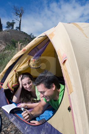 Couple Camping in Tent, Looking Out stock photo, Young couple lying in a tent looking out smiling. by Orange Line Media