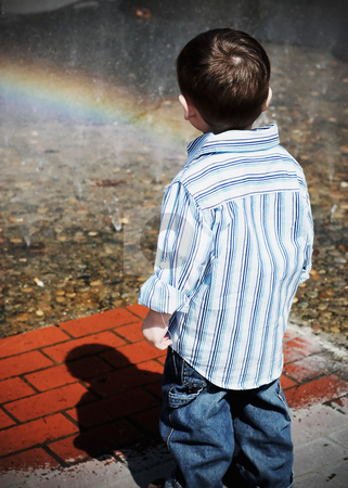 Staring at Rainbows stock photo, Cute young boy in a white shirt and blue jeans staring at a rainbow on a sunny day by Orange Line Media