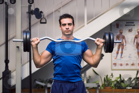 Lifting Barbell Weights stock photo, Male weightlifter, looking straight into camera, holding barbell weights. by Orange Line Media