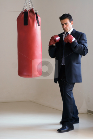 Tough Competitor stock photo, Young attractive businessman in a suit wearing boxing gloves standing ready in front of a heavy punching bag by Orange Line Media