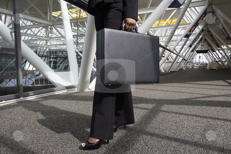 Woman with Briefcase stock photo, Close up of a businesswoman's legs and briefcase as she strides through an office lobby. Horizontally framed shot. by Orange Line Media