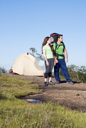 Couple Backpacking - Standing stock photo, Young backpacking couple standing on a mountain taking in the scenary. by Orange Line Media