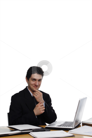 Devilish Businessman stock photo, Businessman sitting at a desk holding grabbing his chin with a devilish look on his face.  Vertical isolated on white. by Orange Line Media