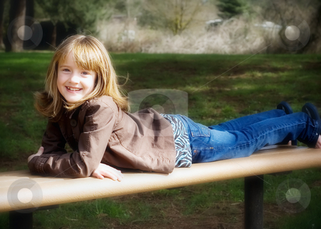 Young Blonde Girl - Horizontal stock photo, Cute young girl stretched out on a park bench. Horizontally framed image shot with a soft focus by Orange Line Media