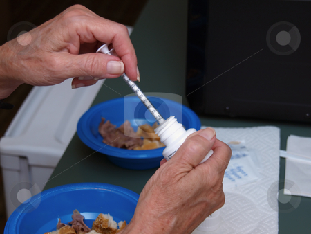 Preparing a Shot - Horizontal stock photo, A woman preparing a shot of insulin at home. by Orange Line Media