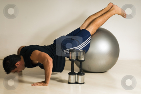 Pushups on using Balance Ball - Horizontal, Isolated stock photo, Male athelete with his knees on balance ball doing pushups. by Orange Line Media