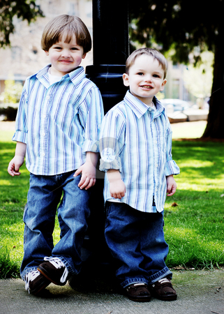 Brothers in the Park - Vertical stock photo, Two brothers dressed identically in a striped shirt and blue jeans standing shoulder to shoulder in a park. High-key style, vertically-framed shot. by Orange Line Media