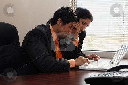 Business Team Looking Stumped stock photo, Male and female business colleagues working together on a hard problem. They have a strained expression on their faces by Orange Line Media