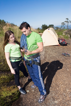 Camping Couple stock photo, Attractive couple checking out their climbing gear while on a camping trip by Orange Line Media