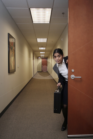 Businesswoman and her briefcase - vertical stock photo, Businesswoman looking around suspiciously with a briefcase in hand in an empty hallway by Orange Line Media
