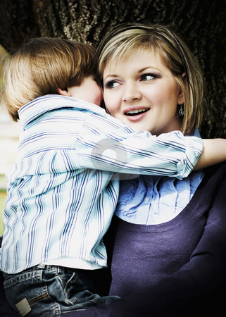 Mother and Son stock photo, Cute young mother with her son in her arms. Vertical, high-contrast shot by Orange Line Media