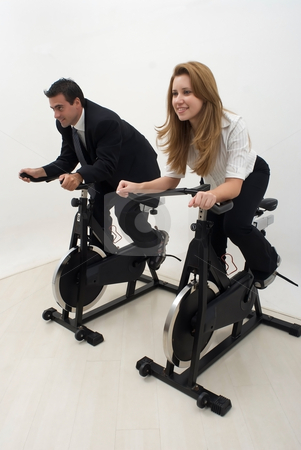 Riding Bikes stock photo, Zoomed out vertically composed shot of two businesspeople (male and female) working out on exercise bikes. Isolated by Orange Line Media