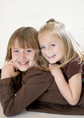 Two Sisters Posing stock photo, Two cute young sisters posing together in a studio. Vertically framed shot isolated against a white studio background. by Orange Line Media