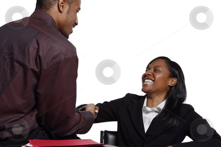 Businesspeople Shaking Hands stock photo, Male and female business colleagues smiling broadly and shaking hands by Orange Line Media