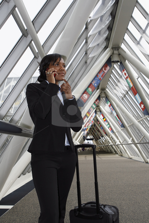 Businesswoman talking on her cellphone stock photo, Vertically framed shot of a businesswoman stopping in a lobby while talking on her cellphone. She appears to be lost in thought and she has her rollaboard luggage with her. by Orange Line Media