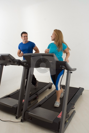 Couple at the Gym - Vertical stock photo, Attractive young couple working out together at the gym on treadmills. Vertically framed shot by Orange Line Media