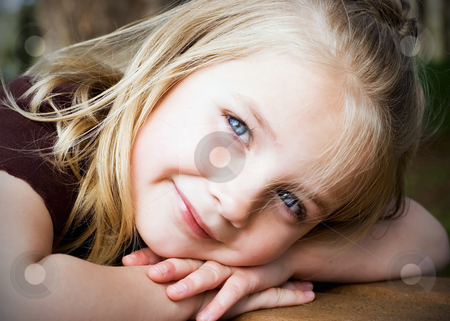 Young Blonde Girl stock photo, Cute blond girl resting her head on her arms smiling at the camera by Orange Line Media