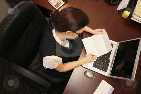 Woman Reading a Letter - Overhead stock photo, Horizontally framed overhead shot of a businesswoman at her desk reading a letter by Orange Line Media