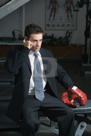 Businessman, Gym, Cellphone stock photo, A shot of businessman in a gym, wearing a suit, taking a call on his cellphone. by Orange Line Media