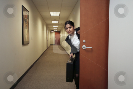 Businesswoman and her briefcase - horizontal stock photo, Businesswoman looking around suspiciously with her briefcase in hand in an empty hallway by Orange Line Media