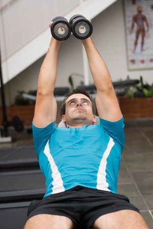 Dumbbell Butterflies stock photo, Male weightlifter, lying down, doing dumbbell butterflies to exercise his chest. by Orange Line Media