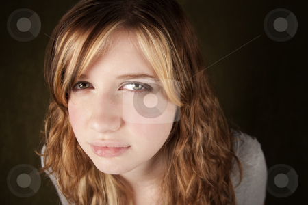 Skeptical Teenage Girl stock photo, Close up of skeptical teenage girl on green background by Scott Griessel