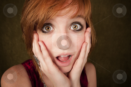 Shocked young girl on a green background stock photo, Shocked pretty young girl with red hair on a green background by Scott Griessel