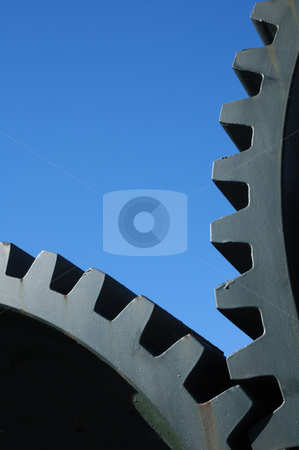Gears stock photo, Two old interlocking gear wheels,  slightly rust-streaked, from an abandoned piece of machinery, set against a clear blue sky. Space for text. by Alistair Scott