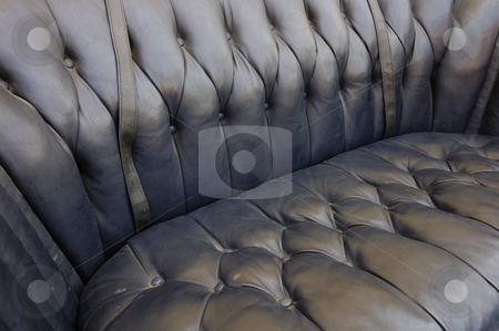 Black leather seat. stock photo, Close-up of an old seat upholstered in black leather. by Alistair Scott