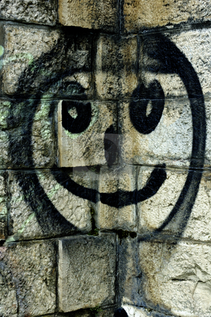 Smiley face on a stone wall stock photo, Illegal graffiti - a smiley face spray-painted in a corner of a stone wall. by Alistair Scott