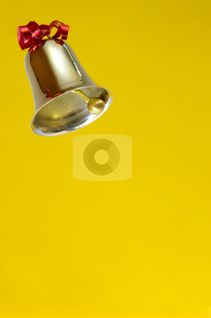 Ringing bell on yellow background stock photo, A ringing bell, decorated with a red ribbon. on plain yellow background, Space for text. by Alistair Scott