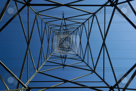 Metal web. stock photo, Inside an electricity pylon looking directly up at the clear blue sky. It is as if the pylon forms a metal spider's web. A tiny aeroplane seems to be caught in the bottom left corner. by Alistair Scott