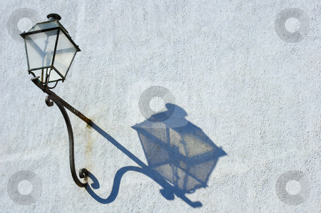 Lamp and shadow. stock photo, An antique street lamp, on a rusting iron support, casts its shadow in the afternoon sun. Rust stains on the wall. Space for text. by Alistair Scott