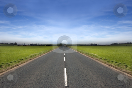 Long Road stock photo, Long road stretching out into the distance under a dramatic blue sky by Peter Cox