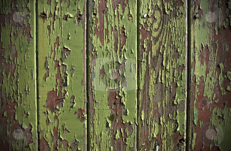 Green paint peeling from a wooden panel door stock photo, Green paint peeling from a wooden panel door showing the wood grain and old red painted surface by Peter Cox