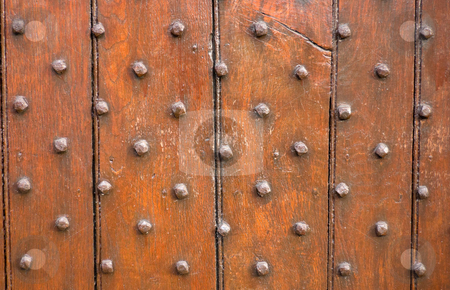 Wooden Door Panel stock photo, Brown wooden door panel with metal stud pattern by Peter Cox
