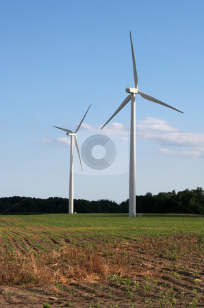 Facing the Future stock photo, Two wind power generators in a field shot against a blue sky. by Chris Hill