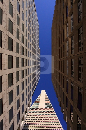 Looking up between two highrise buildings stock photo, Architectural buildings of large city in a down town area, office locations by Richard Clack