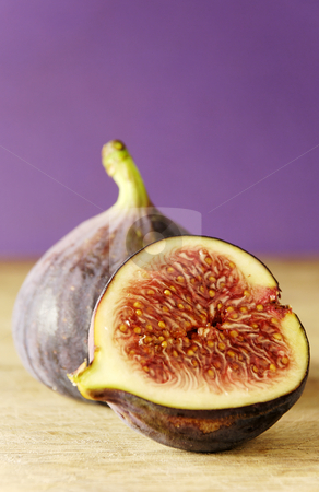 Fig and a half stock photo, Whole and half a fig on wooden chopping board by Paul Turner