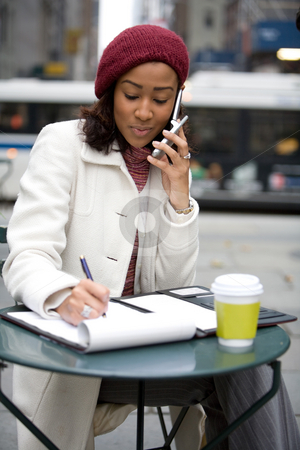Woman On Her Cell Phone stock photo, An attractive business woman talking on her cell phone and writing something down in her notes. by Todd Arena