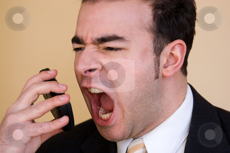 Furious Business Man stock photo, A business man is furiously screaming into his cell phone. by Todd Arena