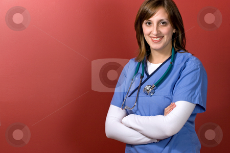 Young Woman Doctor stock photo, A young woman doctor with her arms crossed isolated over a red background by Todd Arena