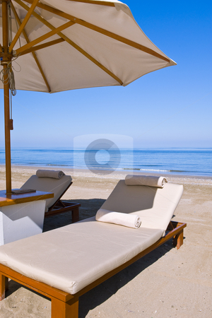 Deck chairs on the beach stock photo, Idyllic scene of deck chairs under an umbrella on a clean beach in the hot afternoon sun. by Nicolaas Traut